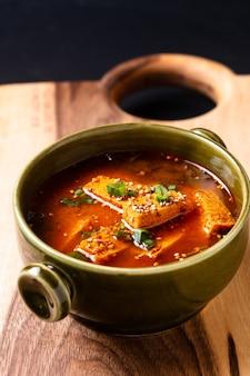 Lebensmittelkonzept koreanische würzige tofusuppe auf holzbrett mit kopierraum
