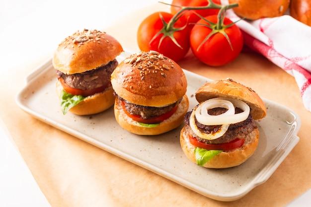 Lebensmittelkonzept selbst gemachte rindfleischhamburger dienen auf quadratischer platte auf weiß mit kopienraum