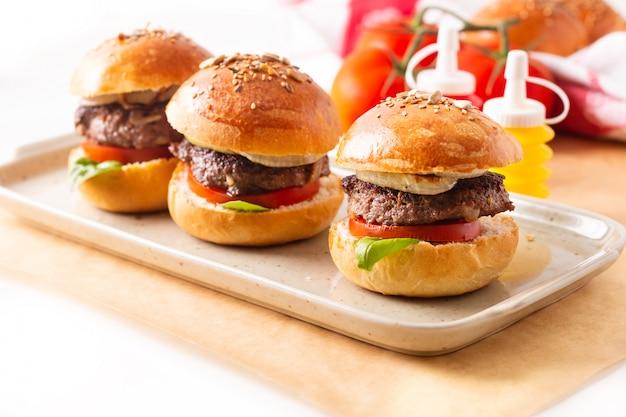 Lebensmittelkonzept selbst gemachte rindfleischhamburger dienen auf quadratischer platte