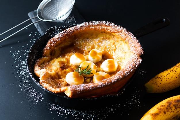Lebensmittelkonzept selbst gemachter niederländischer babybananen-karamellbelagspfannkuchen im bratpfanneneisen warf auf schwarzes