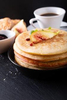 Lebensmittelkonzept selbst gemachter organischer pfannkuchenstapel mit feigenfrühstück auf schwarzem
