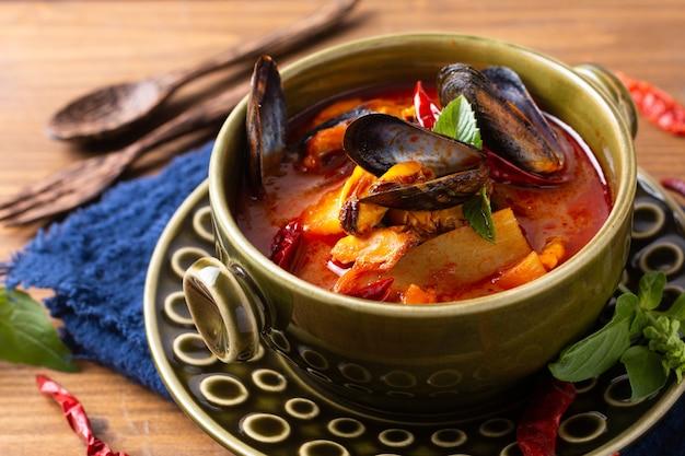 Lebensmittelkonzept thailändisches saures rotes curry muscheln ananas kang kua hoi in grüner keramikschale auf blauem serviettenholzhintergrund mit kopienraum