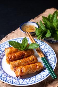 Lebensmittelkonzept vietnamesische gebratene reispapierfrühlingsrollen mit minzen auf schwarzem hintergrund mit kopierraum