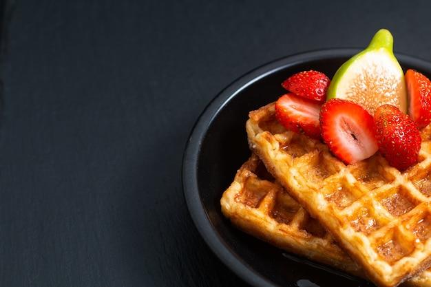 Lebensmittelkonzeptquadratwaffeln und -sirup mit erdbeere und feige mit kopienraum
