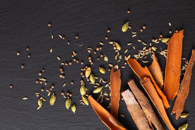 Lebensmittelkonzeptzusammenstellung orientalische gewürzkardamomhülsen, koriandersamen, fenchel und zimt cassia bark sticks auf schwarzem schiefer