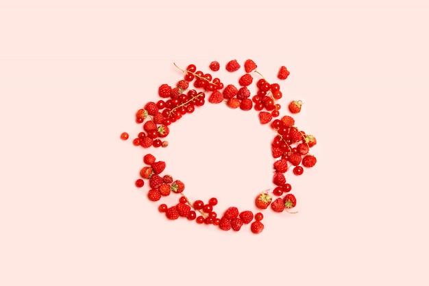 Lebensmittelkreisrahmen von roten reifen johannisbeeren, von erdbeeren und von himbeeren