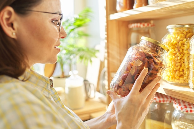 Lebensmittellagerung in der speisekammer, frau, die glas trockener sonnengetrockneter äpfel in der hand hält