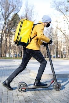 Lebensmittellieferant auf einem roller in einem park. schwarze medizinische maske, gelber rucksack und jacke. winter