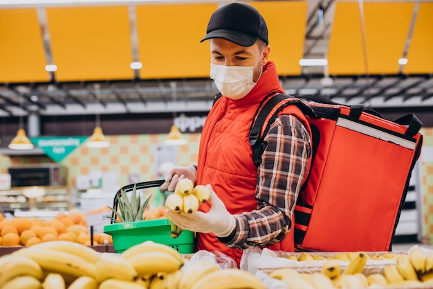 Lebensmittellieferant, der produkte im lebensmittelgeschäft kauft