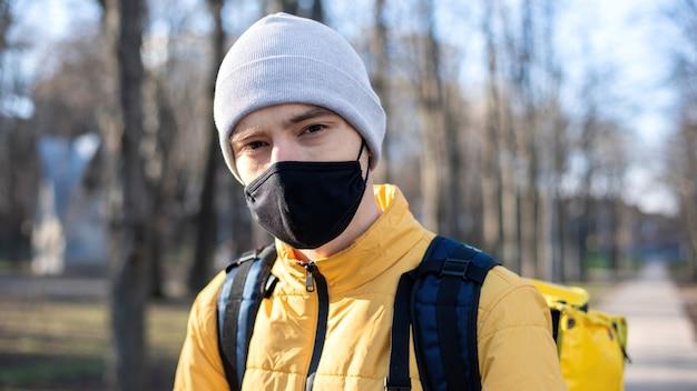 Lebensmittellieferant in einem park. schwarze medizinische maske, gelber rucksack und jacke. winter