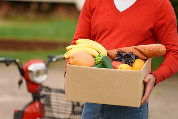 Lebensmittellieferant in roter uniform mit einer kortonbox mit lebensmitteln in seinen händen