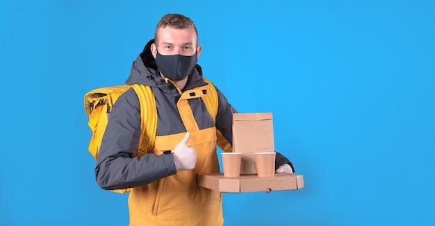 Lebensmittellieferant mit einer medizinischen maske in einer gelben jacke