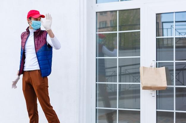 Lebensmittellieferant mit medizinischen handschuhen und gesichtsmaske. online-shopping und lieferung für lebensmittel, wein und lebensmittel. selbstquarantäne während der coronavirus-pandemie. kurierdienst für essenslieferungen