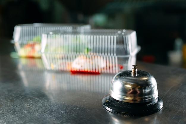 Lebensmittellieferservice. verteilungstisch in einem restaurant mit einer metallglocke. lebensmittel in plastikbehältern. panna cotta und gemüsesalat in einwegbehältern aus kunststoff.