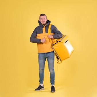 Lebensmittellieferung junger mann in einer gelben jacke
