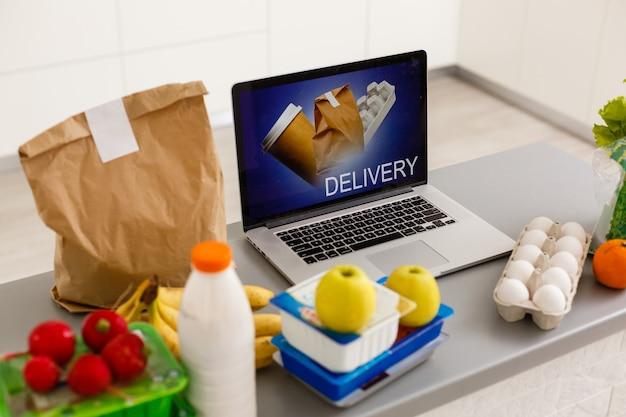 Lebensmittellieferung lebensmittel-laptop auf dem tisch. warmer ton