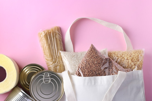 Lebensmittellieferung, spende, textil-einkaufstüte mit lebensmittelvorräten krisenlebensmittelbestand für quarantäne-isolationszeit auf rosa oberfläche. reis, buchweizen, nudeln, konserven, toilettenpapier, draufsicht