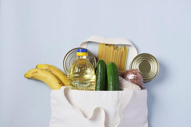 Lebensmittellieferung, spende. textilbeutel mit nahrungsmitteln auf blauem hintergrund.