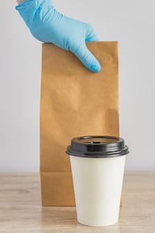 Lebensmittellieferung während. lieferservice. weibliche hand in medizinischen handschuhen, die leere leere bastelpapierrückseite neben wegwerfbarer kaffeetasse auf dem tisch halten