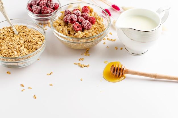 Lebensmittelmenü der ausgewogenen diät zum frühstück mit haferbrei rollen mit himbeeren und honigschöpflöffel