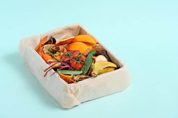 Lebensmittelmüll, gemüseschalen im kompostbehälter auf blauem hintergrund, kompostkonzept. kopieren sie platz, nachhaltig und ohne abfall,