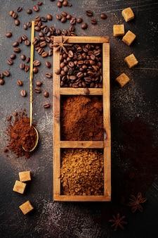 Lebensmitteloberfläche mit drei kaffeesorten: bohnen, gemahlen, sofort in holzkiste auf alter brauner betonoberfläche. rustikaler stil. selektiver fokus. draufsicht.