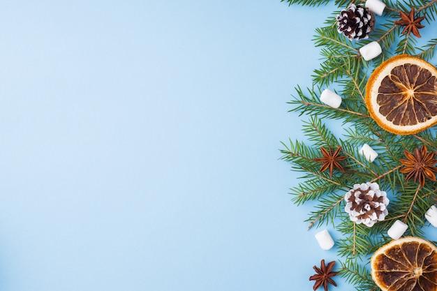Lebensmittelorangennussgewürz-kiefernkegel weihnachtsbaum auf blau