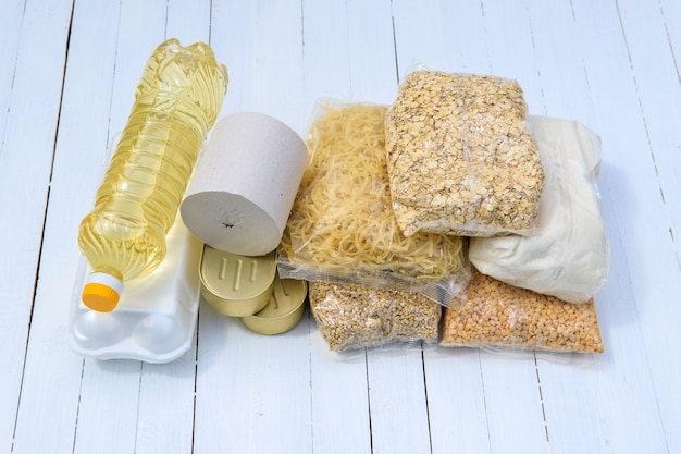Lebensmittelspende für bedürftige. satz müsli, ovianka, perlgerste, erbsen, toilettenpapier, konserven, sonnenblumenöl, eier auf einem weißen hintergrund.