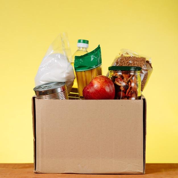 Lebensmittelspendenkonzept. spendenbox mit essen für spenden auf gelbem hintergrund. hilfe für ältere menschen im kontext der coronavirus-pandemie. quadratisches bild
