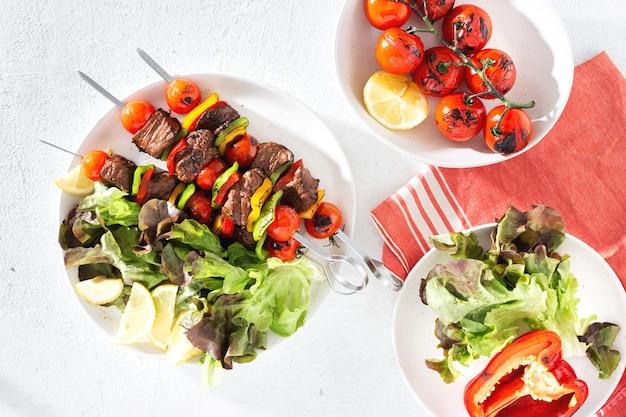 Lebensmitteltabelle mit rindfleisch grillte fleischkebab mit draufsicht des gemüses und der soße