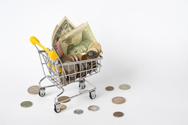 Lebensmittelwagen mit geld aus verschiedenen ländern. münzen fallen aus einem wagen voller geld. währung. wirtschaft, preisanstieg. steigende preise.