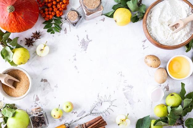Lebensmittelzutaten für die herstellung von herbstkürbiskuchen auf weißem steinhintergrund. hausgemachtes backkonzept. rahmen