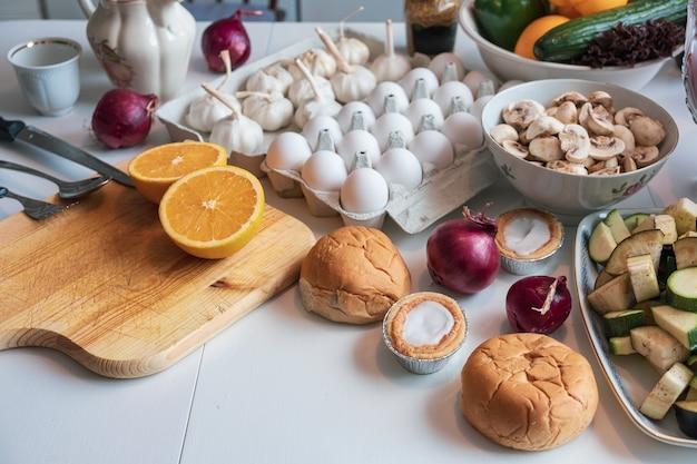 Lebensmittelzutaten mit obst, gemüse, brot und geschirr auf dem tisch