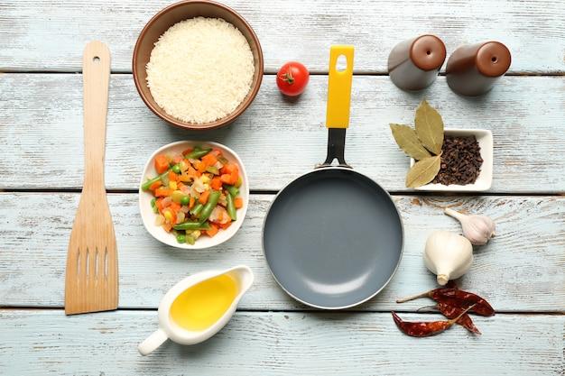 Lebensmittelzutaten und küchenutensilien zum kochen auf holz