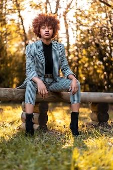 Lebensstil, afro-haariges mädchen im karierten anzug und im schwarzen pullover in einem park mit der sonne im hintergrund