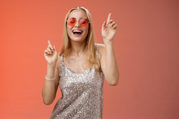 Lebensstil. amüsierte attraktive glückliche lächelnde frau tanzt nachtclub mit spaß genießen gehen wilde party feiern b-tag tragen stilvolle kleid sonnenbrille heben zeigefinger lächelnd mitsingen.