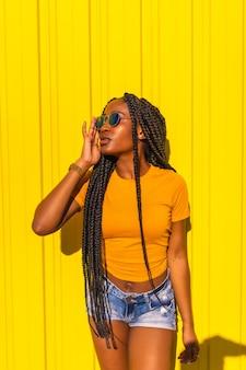 Lebensstil, attraktives schwarzes mädchen mit langen zöpfen, gelben t-shirts und kurzen jeans an einer gelben wand. mit sonnenbrille in der urbanen session in der stadt, trap-tänzerin, die küsse in die luft bläst