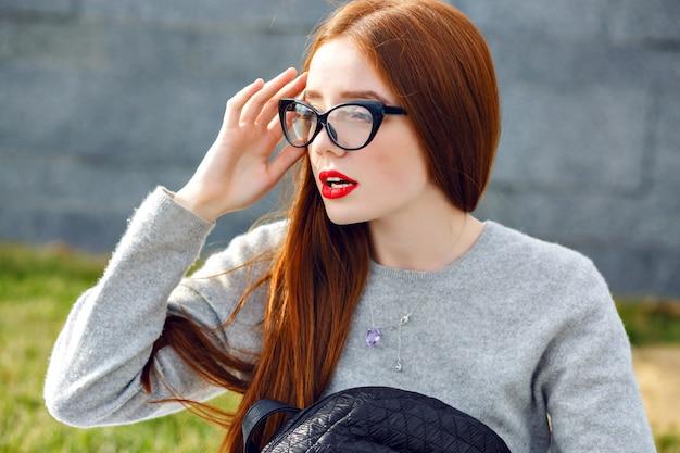 Lebensstil-außenporträt des hübschen ingwermädchens, das klares glas und grauer kaschmirpullover trägt, posierend im park, herbst-winter-stil. einen rucksack halten.