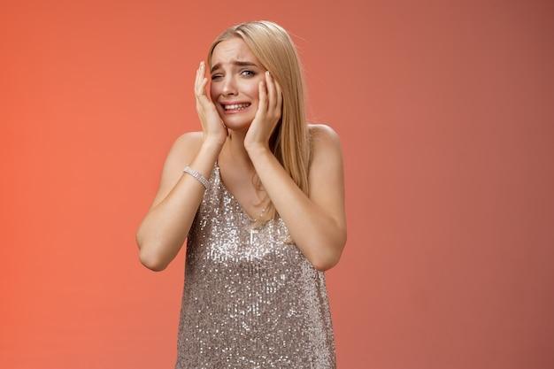 Lebensstil. besorgte blonde freundin panik angst ängstlich unsicher unsicher ängstlich drehen gesichtsbedeckung kopf blick verloren verängstigt angriffsopfer im nachtclub angst stehend erschrocken in silbernen kleid stehen.
