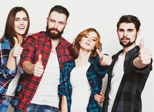 Lebensstil, bildung und menschenkonzept: glückliches team von studenten, die daumen nach oben zeigen. studioaufnahme auf weißem hintergrund. hipster-stil. spezielle tonisierung.