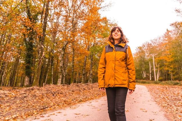 Lebensstil, eine junge brünette in einer gelben jacke, die in einem wald im herbst geht. artikutza wald in san sebastin, gipuzkoa, baskenland. spanien