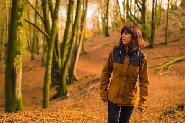 Lebensstil, eine junge frau in einer gelben jacke, die in einem wald im herbst geht. artikutza wald in san sebastin, gipuzkoa, baskenland. spanien