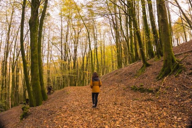 Lebensstil, eine junge frau in einer gelben jacke, die rückwärts entlang eines waldweges im herbst geht. artikutza wald in san sebastin, gipuzkoa, baskenland. spanien