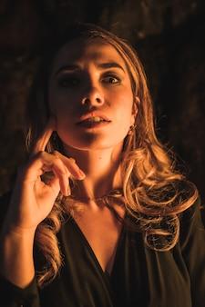 Lebensstil eine junge kaukasische blondine in einem schwarzen kleid in einer höhle mit gelbem licht beleuchtet sehr verführerisches porträt des modells