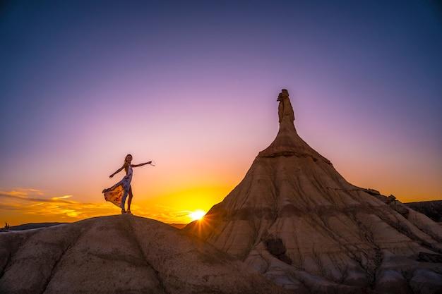 Lebensstil einer jungen blonden frau im weißen kleid und in den blumen in der bardenas-wüste bei sonnenuntergang
