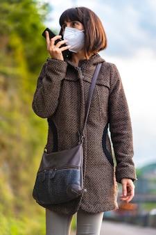 Lebensstil einer jungen brünette mit maske, die eine audio-nachricht sendet. erste spaziergänge der unkontrollierten covid-19-pandemie