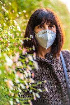 Lebensstil einer jungen brünette mit maske neben schönen gänseblümchen. erste spaziergänge der unkontrollierten covid-19-pandemie