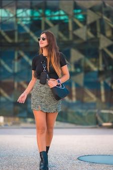 Lebensstil einer jungen kaukasischen brünetten geschäftsfrau außerhalb des bürogebäudes zu fuß. mit grünem rock und sonnenbrille