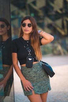 Lebensstil einer jungen unternehmerin caucasica brünette außerhalb des bürogebäudes. mit grünem rock und sonnenbrille