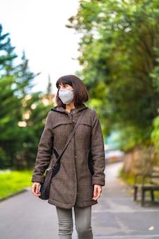 Lebensstil einer kaukasischen brünette mit kurzen haaren und maske, die in einem park gehen. erste spaziergänge der unkontrollierten covid-19-pandemie